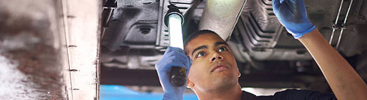 Inspecting the underside of a vehicle during an MOT test