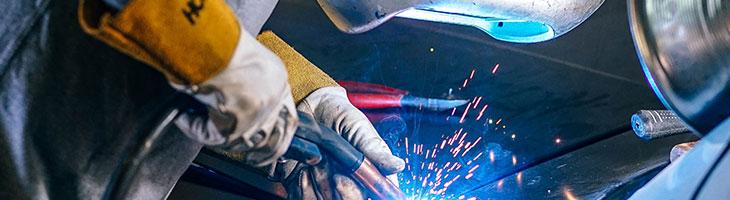 Welder fixing a category D car