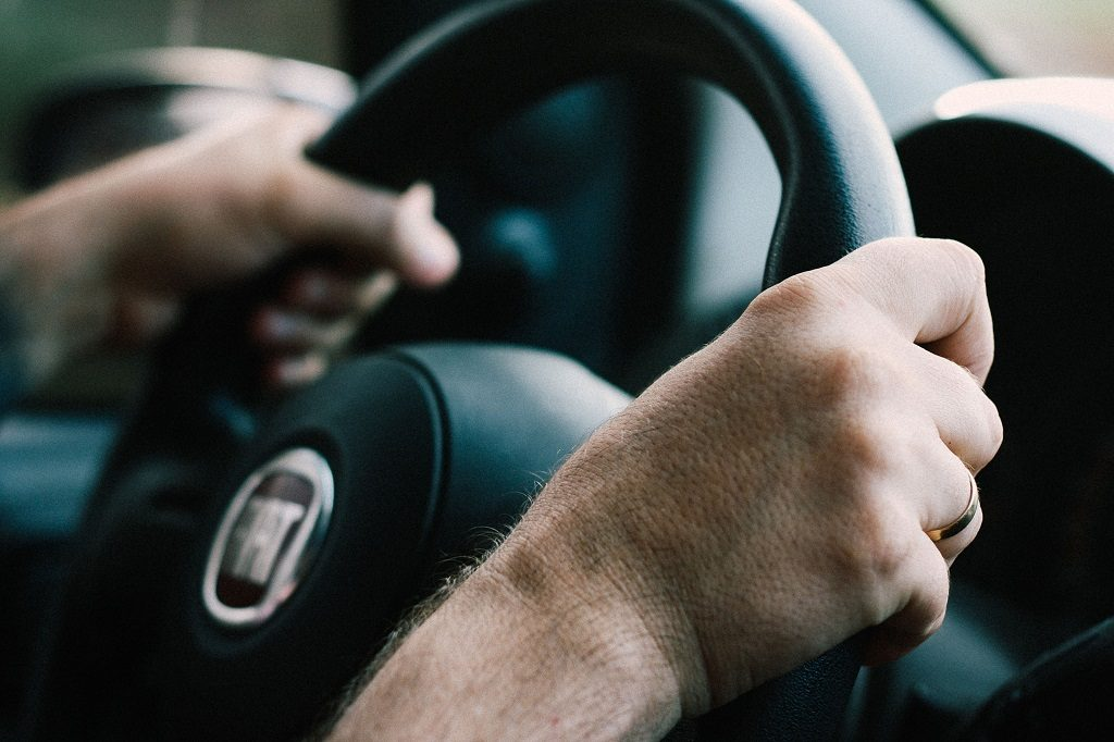 Close up of driver's hands on a steering wheel as they drive in the EU.