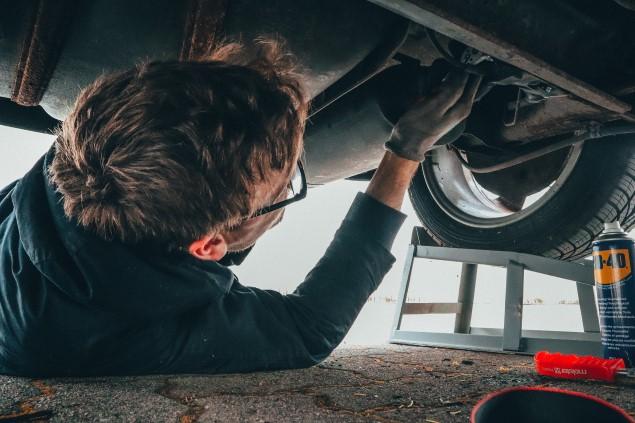 Mechanic under car during an MOT inspection